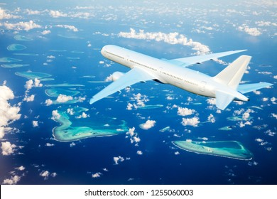 The plane flies over the Maldives islands. View of a flying plane.