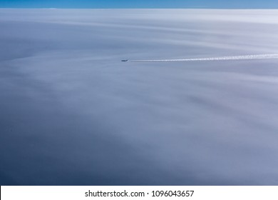 A plane flights  above the thick layer of clouds.