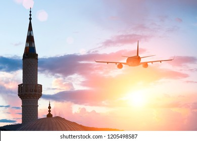 A plane flying in the evening sky above the minaret