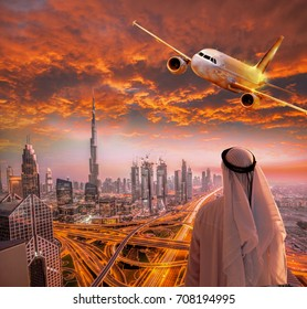 Plane is flying over Dubai against colorful sunset in United Arab Emirates