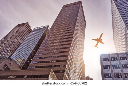 plane flying over futuristic glass and steel office towers in the sun, Manhattan, New York City