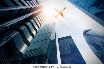 plane flying over highrise office buildings in the sun, financial district London, Great Britain