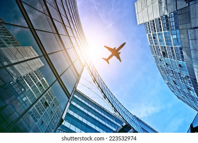 plane flying over modern glass and steel office buildings near Potsdamer Platz, Berlin, Germany