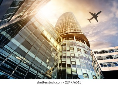 plane flying over modern office tower