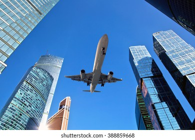 The plane is flying very low over the skyscrapers