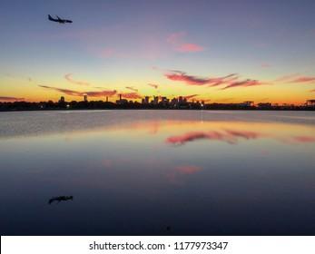 Plane landing at Logan airport during sunset