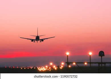 Plane landing at runway on the background of red sunset