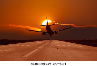 Plane landing in a sunset