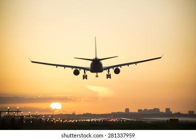 Plane landing when sunrise started.