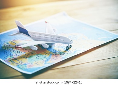 Plane model with world map as airplane traveling concept