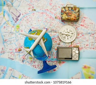 plane on globe, photo camera, compass, suitcase lie paper map. vintage case with stickers. travel background. airplane fly above earth.