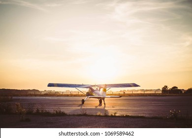 Plane on the runway in the rays of the sun