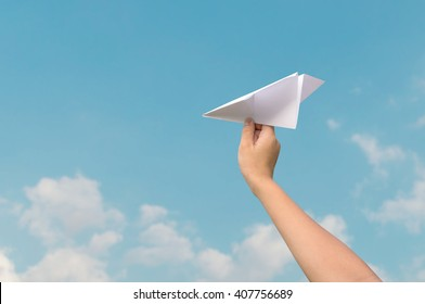 plane paper in children hand and blue sky in cloudy day. business concept.