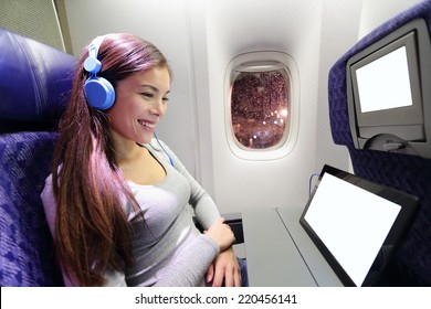 Plane passenger in airplane using tablet computer. Woman in plane cabin using smart device listening to music on headphones.