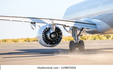 The plane is preparing to fly at the airport. Airplane on the runway at the airport. The turbine of the aircraft is warming up, the landing gear is preparing for flight. The plane flies in the sky.