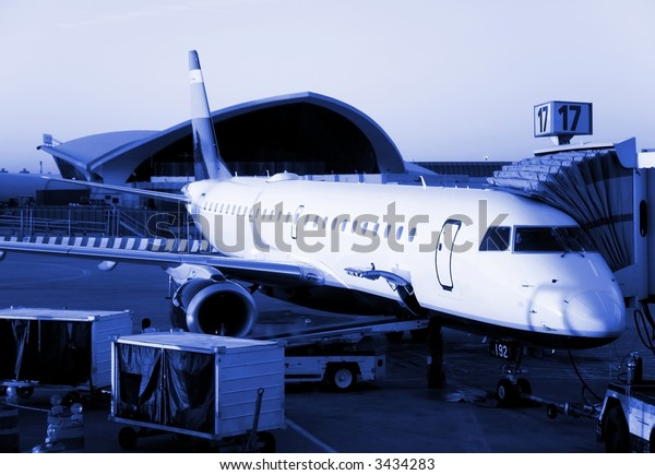 Plane ready for departure, early morning flight.  Blue monochrome