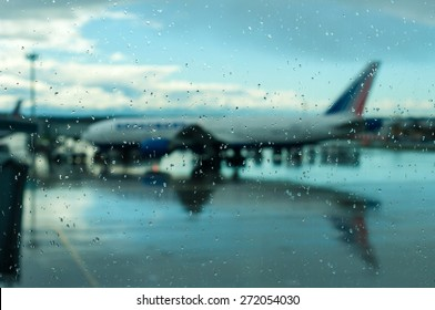 Plane silhouette of the covered glass raindrops. Flights transferred to a later time because of bad weather.
