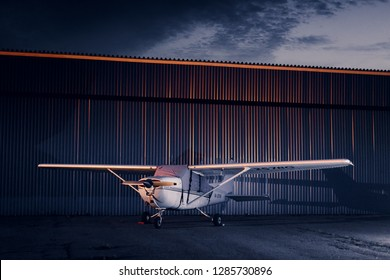 the plane is standing at the hangar at night