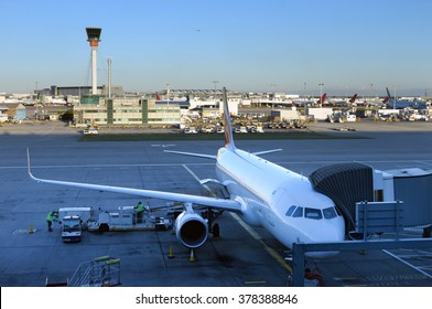 The plane stands at the tunnel at the airport in London. Aircraft is prepared for departure from Heathrow airdrome.