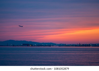 A plane takes off from the Kansai International Airport in Osaka Japan at sunset. KIX is built on an artificial island in the middle of the Osaka Bay an is completely surrounded by the sea.