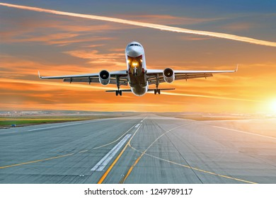 The plane takes off from the runway in the evening at the airport