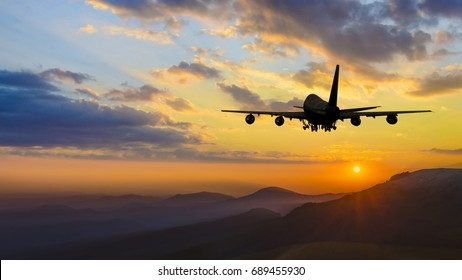 Plane taking off over mountain range at sunset