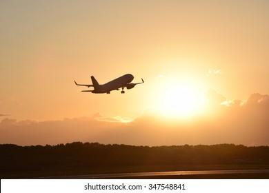 Plane taking off - sunset background