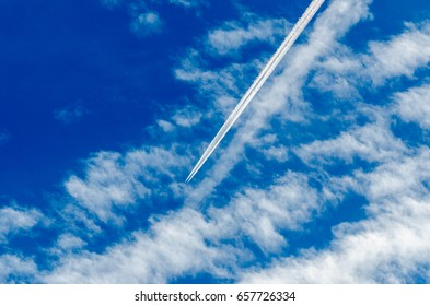 plane traveling on bright, blue sky with fluffy clouds