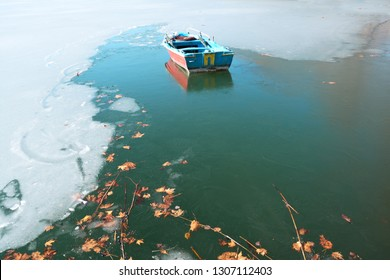 Plane tree leaves and fishing boat trapped in icy water of lake Orestiada in Kastoria,Greece