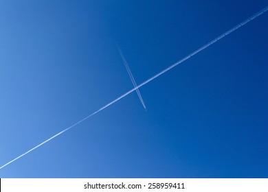 Plane vapor trails crossing in sky