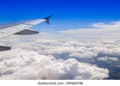 Plane view from the window on picturesque white clouds and wing of the plane