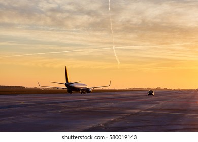 Plane waiting to take off against stunning sunrise