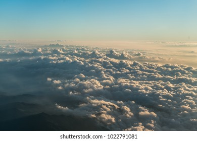 Plane window view with blue sky and clouds.