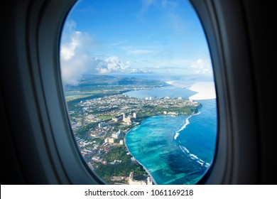 Plane window view with blue sky and sea