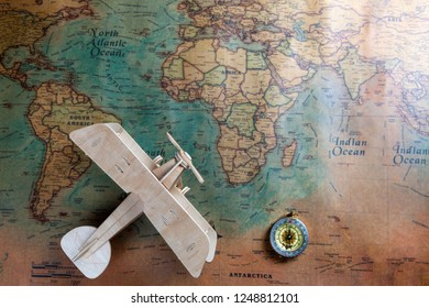 a plane of wood, a compass on the background of the map