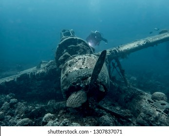 Plane wreck from World War II in Palau, Micronesia sitting on ocean bottom with diver swimming past wreck.