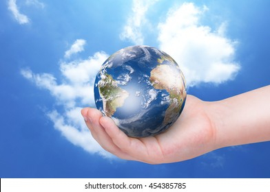 Planet Earth in baby girl's hand over blue sky background. Ecology concept, conservation environment
