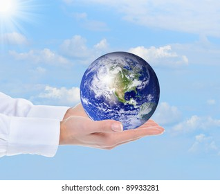 Planet Earth in the female hand against the sky