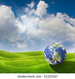 Planet Earth goes on a vacation at a beautiful green meadow. Beautiful spring sunny day with blue cloudy sky