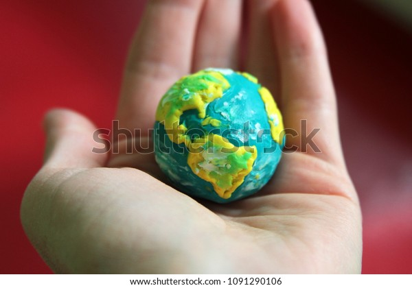 planet earth made of plasticine in hand