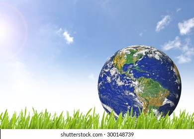 Planet Earth on beautiful green grass and sunny day with blue cloudy sky - Elements of this image furnished by NASA