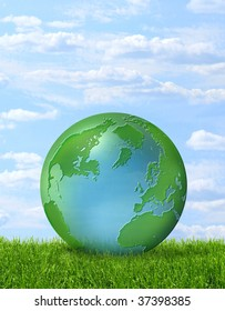 planet earth on green growing grass, on blue sky background