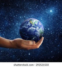 Planet earth on palm and space background. Conceptual Image. Elements of this image furnished by NASA