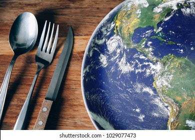 The planet Earth plate with a spoon, fork and knife on a wooden background. World hunger concept. Feed the world.