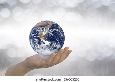 Planet in human hand over blurred beautiful  nature background. Earth Day, Elements of this image furnished by NASA.