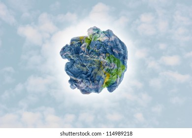 Planet paper trash over a cloudy sky background as a metaphor for environmental issues and concepts.