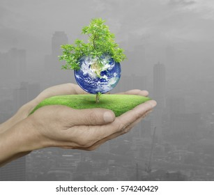 Planet and tree in human hands over pollution city, Save the earth concept, Elements of this image furnished by NASA