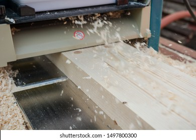 planing boards on a thicknesser. wood shavings. machine for planing wood. carpentry work. joiner's machine. wood processing.