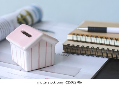 Planing for budget of renovation the home. The little home model and notebooks with a pen on the table with home magazine.