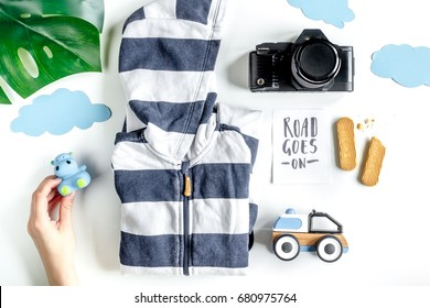 planing trip with child with clothes and camera white background top view